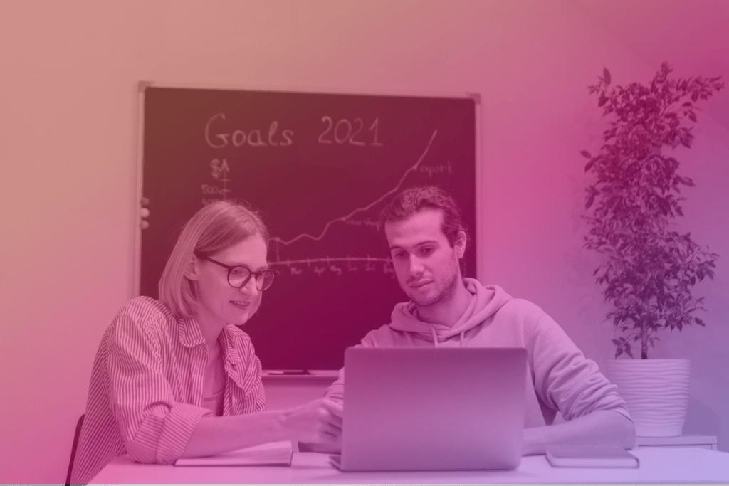 Zdjęcie: dwie młode osoby siedzą przy laptopie, wtle tablica popisana kredą iroślina wdoniczce. Razem tłumaczą kampanie Google Ads.